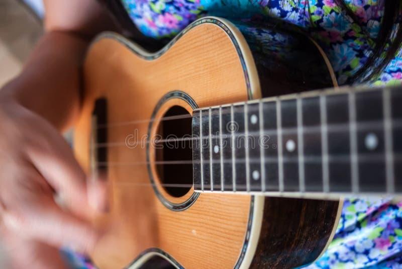 Slut upp av kvinnan som spelar ukulelet arkivfoto