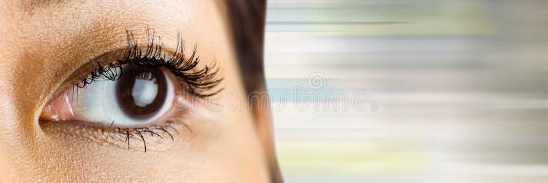 Slut upp av kvinnas öga med linsen och oskarp grå bakgrund arkivbild