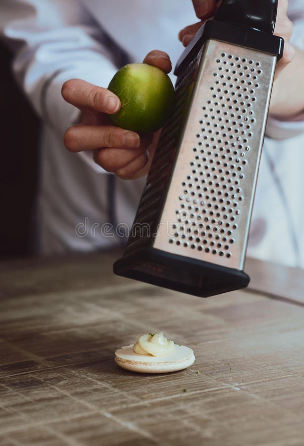 Slut upp av kvinnliga konditor hand som lagar mat den läckra makron arkivfoto