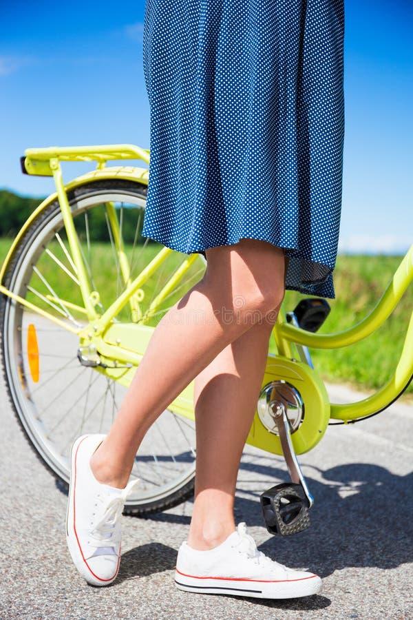Slut upp av kvinnligben och den retro cykeln royaltyfria foton