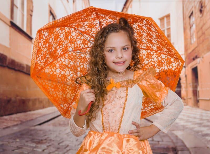Slut upp av lilla flickan som bär en härligt kolonialt dräkt och innehav ett orange paraply och poserar med en hand in royaltyfri foto