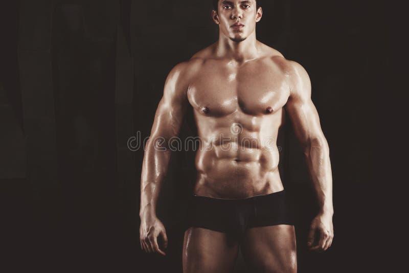 Slut upp av lyftande vikter för ung muskulös man över mörk bakgrund fotografering för bildbyråer
