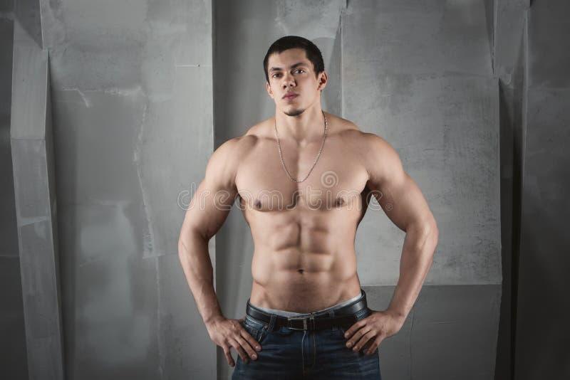 Slut upp av lyftande vikter för ung muskulös man arkivfoton