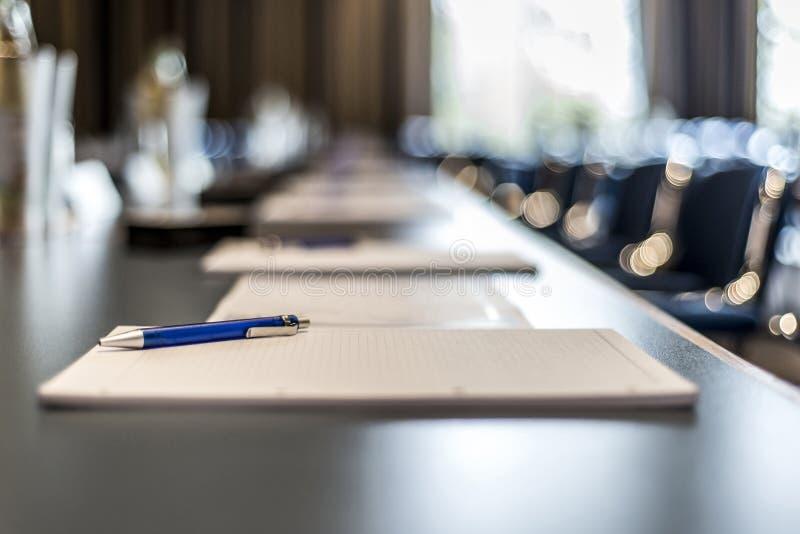 Slut upp av mörka pennor för exponeringsglas för konferenstabellvatten, pappersark och oskarp fönsterbakgrund arkivbild