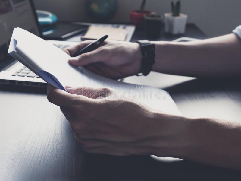 Slut upp av manliga händer som rymmer som är pappers- med pennan på hans kontorsskrivbord royaltyfri bild