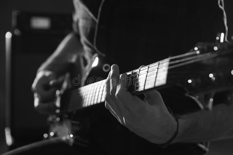 Slut upp av mannen som spelar den elektriska gitarren som skjutas i monokrom royaltyfri foto