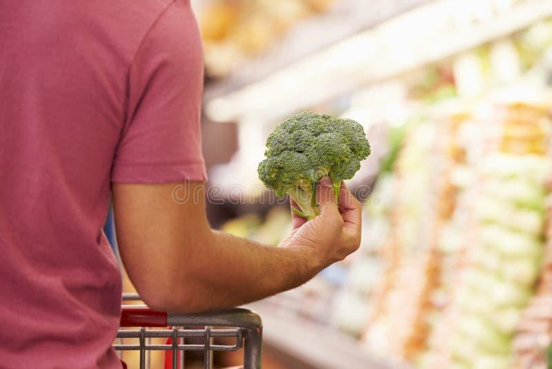 Slut upp av mannen som väljer broccoli i supermarket arkivbilder