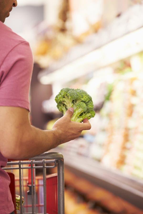 Slut upp av mannen som väljer broccoli i supermarket arkivfoton