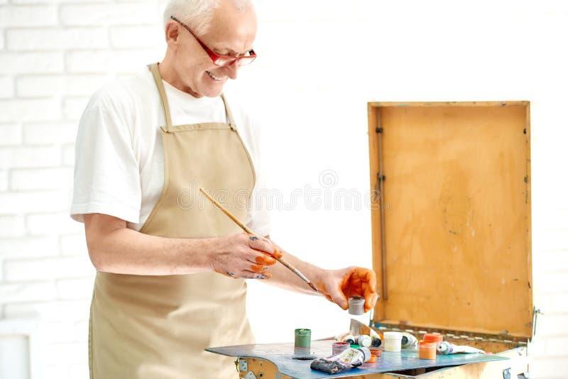 Slut upp av mannen som väljer målarfärger som han behöver måla ny målning arkivfoton