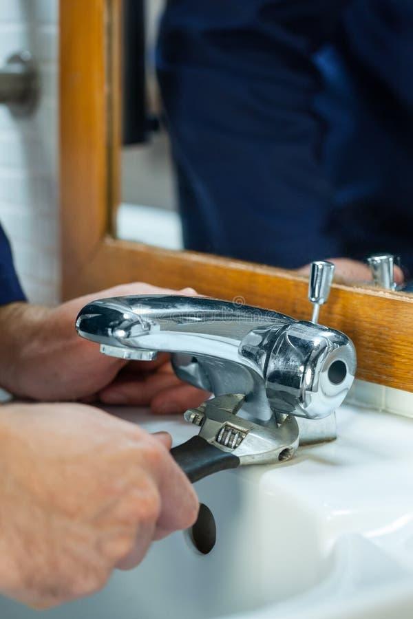Slut upp av rörmokaren som kontrollerar klappet arkivbild