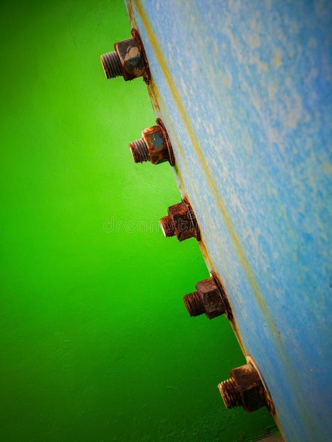 Slut upp av rostfläck på bulten och muttrar med väggen för grön färg arkivfoto