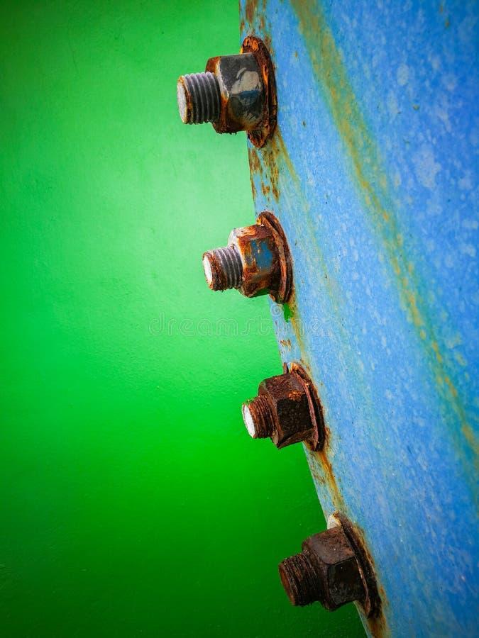Slut upp av rostfläck på bulten och muttrar med väggen för grön färg in royaltyfri fotografi