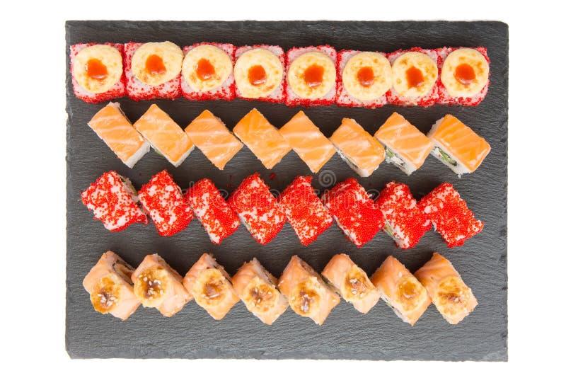 slut upp av sashimisushiuppsättningen med pinnar och sojabönor - sushirulle med lax- och sushirulle med den rökte ålen, selektiv  arkivbild