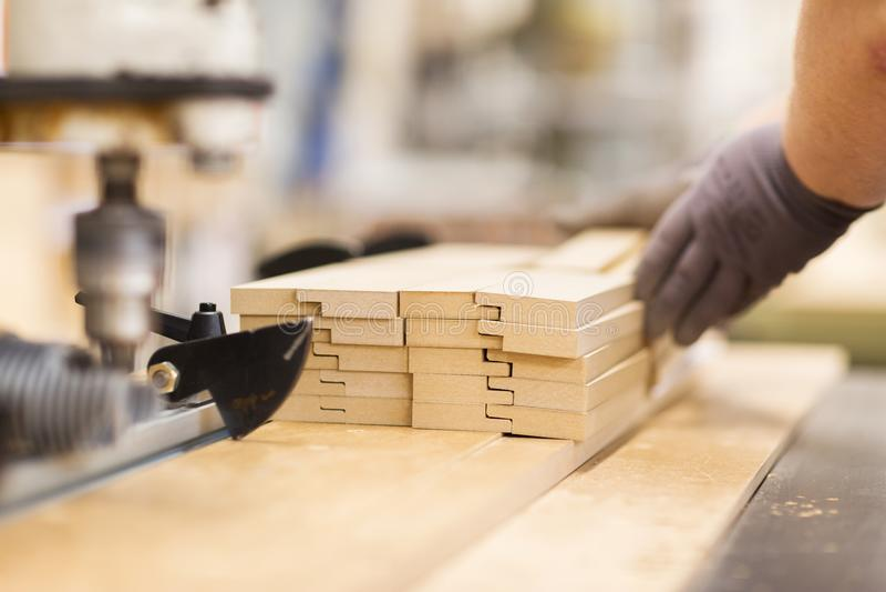 Slut upp av snickarehanden med bräden på fabriken royaltyfri bild