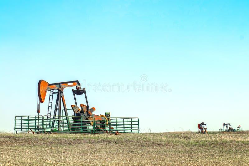 Slut--upp av stålar för oljabrunnpump ut i ett fält inneslutat i allt ett metallnötkreaturstaket med två andra pumpa brunnar i av arkivbild