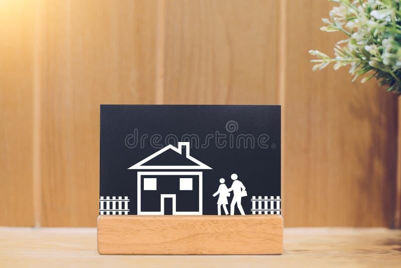 Slut upp av svart tavla med familjen som går att returnera huset på en träbakgrund arkivbild