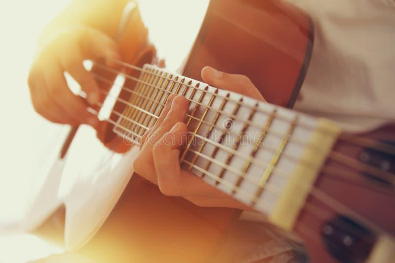 Slut upp av unga flickan som spelar den akustiska gitarren fotografering för bildbyråer