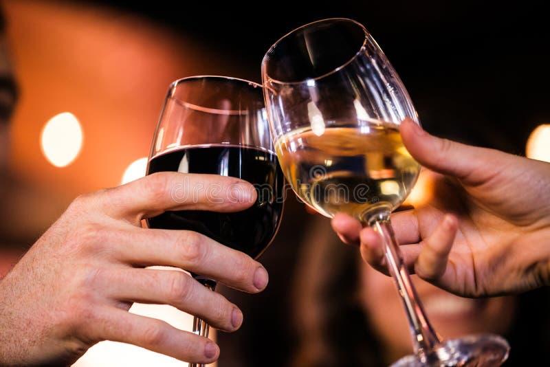 Slut upp av vänner som rostar med vin arkivfoton