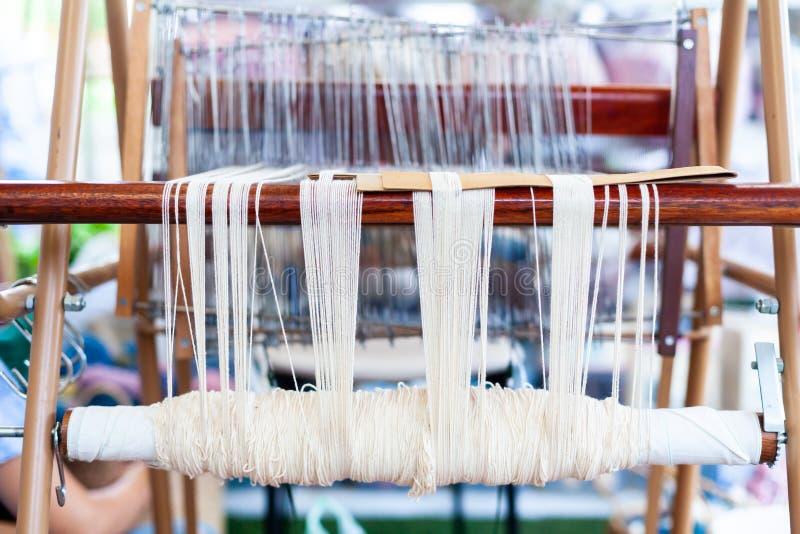 Slut upp av vit linne på den väva maskinen och den thailändska traditioen arkivfoton