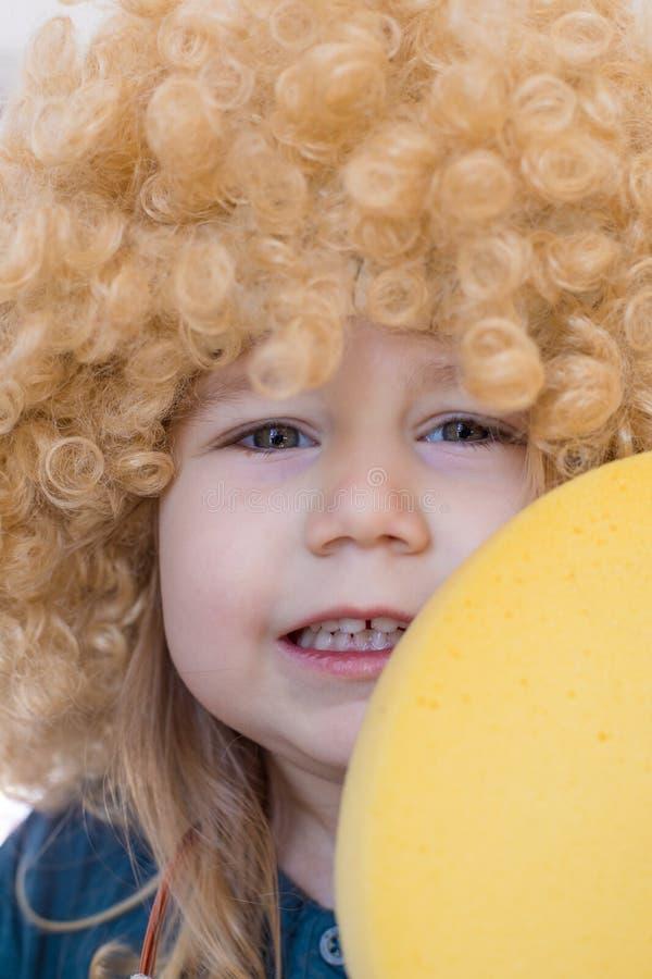 Slut upp barnframsida med den lockiga peruken royaltyfria bilder