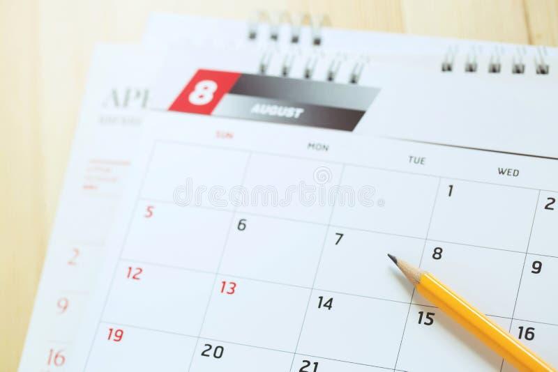 Slut upp blyertspennan för månad för kalendersidanummer den gula august som ska markeras fotografering för bildbyråer