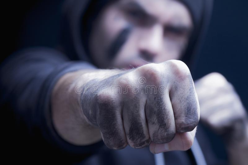 Slut upp den aggressiva mannen som ger en stansmaskin Röveri- och konflictbegrepp Selektiv fokus på näven arkivfoto