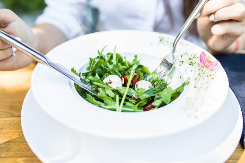 Slut upp den attraktiva kvinnahanden som rymmer gaffeln och skeden till att äta grönsaksallad med en kopp kaffe på lunch i kafé e arkivfoton