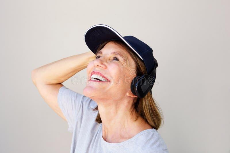 Slut upp den attraktiva mellersta ålderkvinnan som ler med hörlurar arkivbild