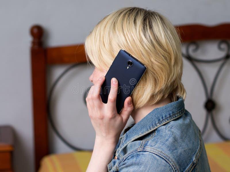 Slut upp den blonda kvinnan som rymmer en mobil royaltyfria foton