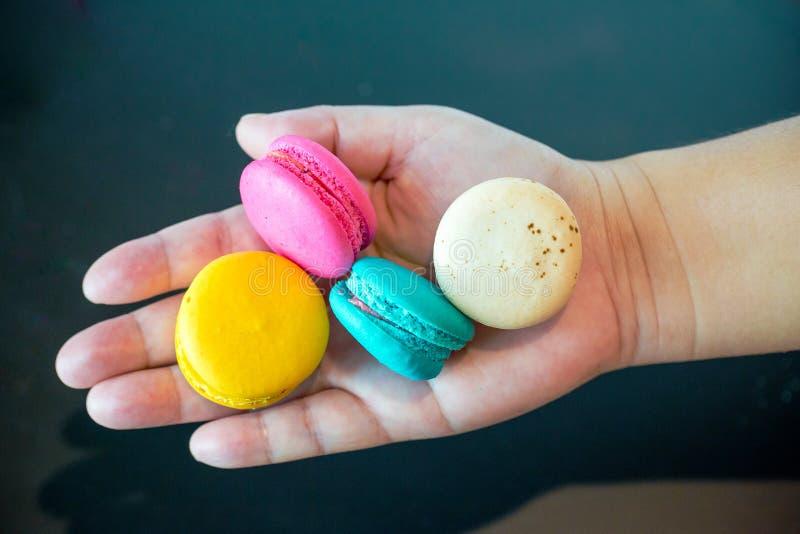 Slut upp den färgrika macaronsefterrätten med tappningtonesonhanden Färgrik fransk macaronsbakgrund, olik färgrik makronbac fotografering för bildbyråer
