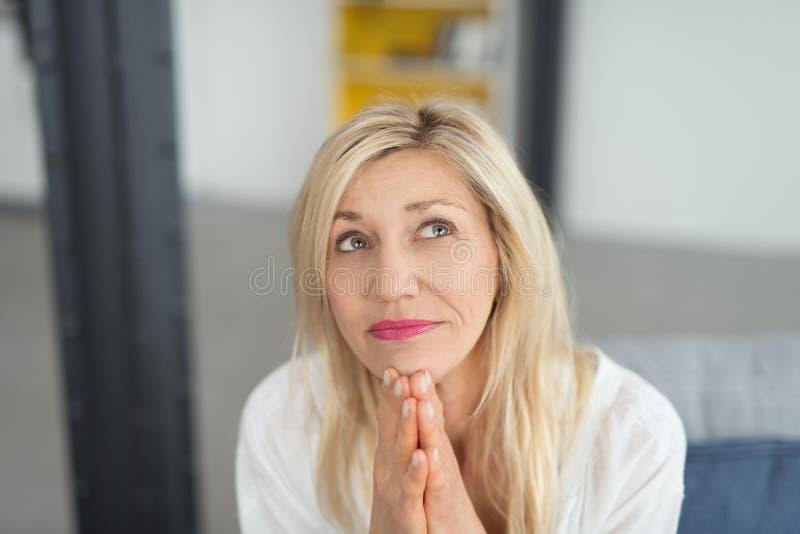 Slut upp den fundersamma blonda vuxna damen Looking Up royaltyfri bild