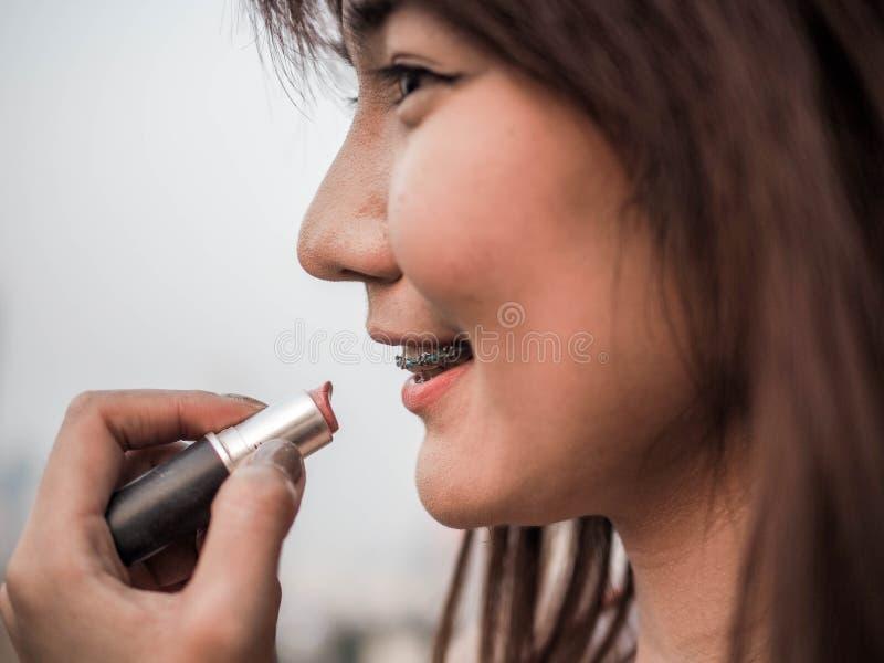 Slut upp den härliga asiatiska kvinnan som sätter makeupläppstift, lyckligt kvinnabegrepp som är filmiskt royaltyfri foto