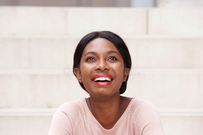 Slut upp den härliga unga svarta kvinnan som skrattar och ser upp royaltyfri bild