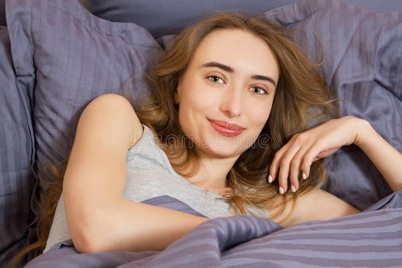 Slut upp den lyckliga tonåriga kvinnan som vaknar upp på sängen i morgonen arkivbild