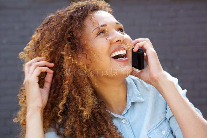 Slut upp den lyckliga unga kvinnan som skrattar och talar på mobiltelefonen fotografering för bildbyråer