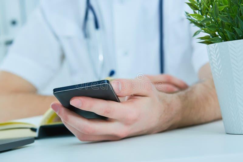 Slut upp den manliga doktorn eller medicinaren som använder den smarta telefonen för mobil som arbetar på bärbar datordatoren i s arkivfoton