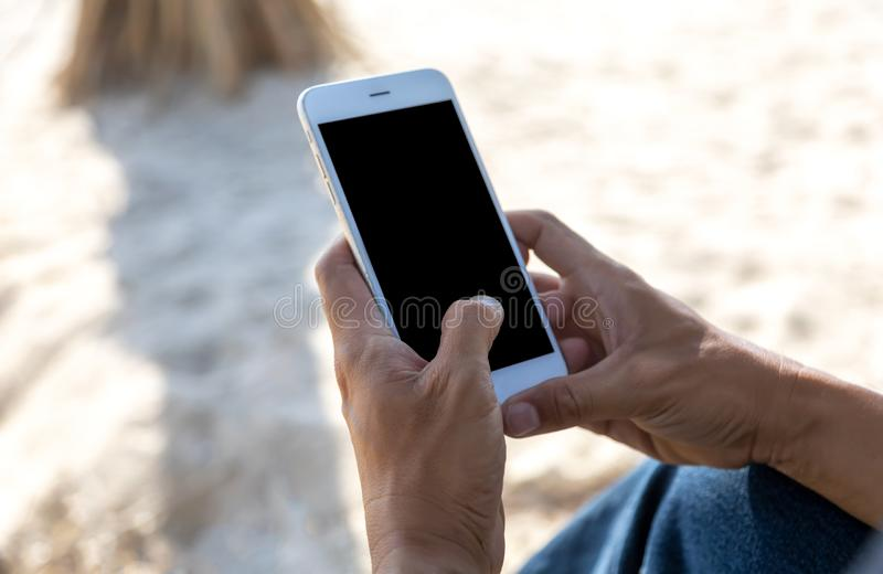 Slut upp den mobila smarta telefonen för handmanbruk på stranden Telefon med den svarta sk?rmen Med kopieringsutrymme f?r text el arkivbilder