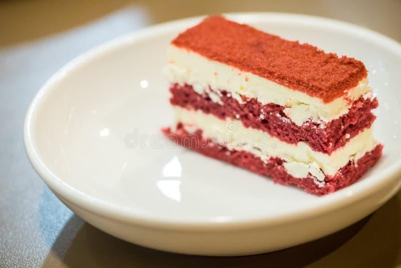 Slut upp den röda sammetkakan i den vita maträtten med pepparmintbladet I royaltyfria foton