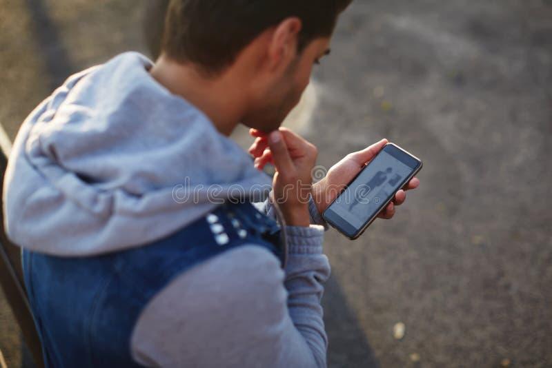 Slut upp den stiliga unga mannen som använder den smarta telefonen, medan stå utomhus på den soliga aftonen arkivfoto