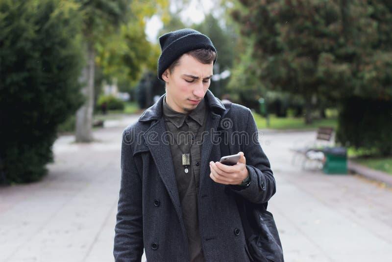Slut upp den stiliga unga mannen som använder den smarta telefonen fotografering för bildbyråer