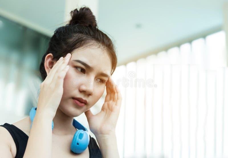 Slut upp den unga asiatiska flickan som har huvudvärk fotografering för bildbyråer