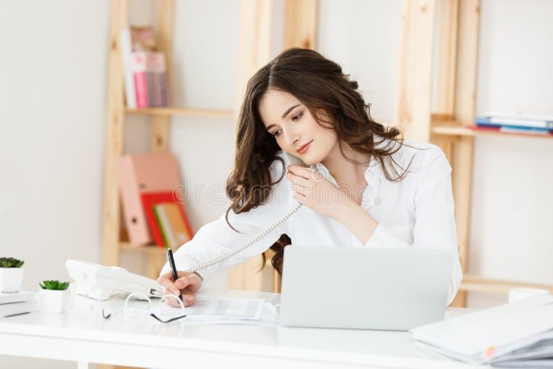 Slut upp den unga kontorskvinnan som talar till någon på hennes telefon, medan se in i avståndet med lyckligt ansiktsuttryck fotografering för bildbyråer