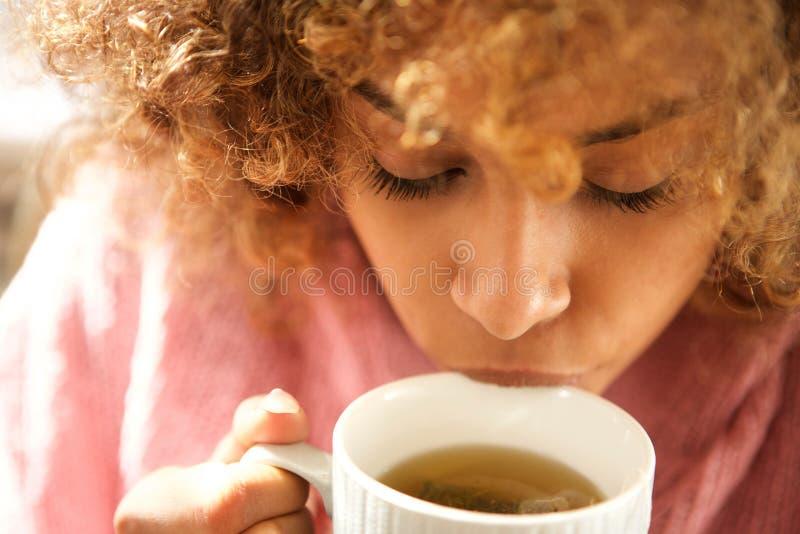 Slut upp den unga svarta kvinnan som dricker kopp te arkivfoton