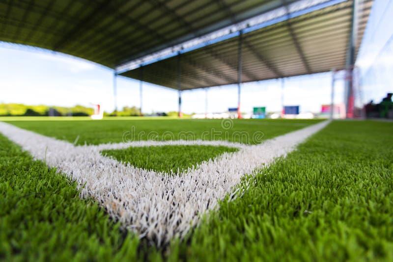 Slut upp den vita linjen hörn på ett gräs för fotbollfält royaltyfri fotografi