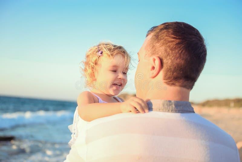 Slut upp den vuxna fadern som rymmer hans lyckliga blondy barnflickadotter på händerna och har gyckel som går på stranden Familjv royaltyfria bilder