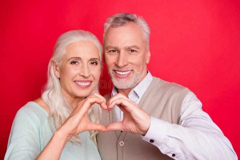 Slut upp det härliga fotoet gulligt henne henne honom honom hans åldriga par för grabbdampartners som gör hjärtadiagramet fingerr royaltyfri bild