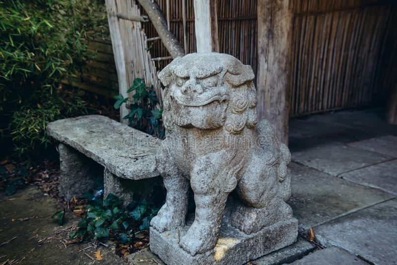 Slut upp det kinesiska imperialistiska lejonet, staty för förmyndarelejonsten, skulptur för kinesisk japansk stil i tempelträdgår royaltyfri fotografi