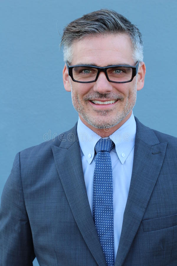 Slut upp dräkten och glasögon för affär för mellersta ålderman som den bärande ler på kameran som isoleras på blå bakgrund royaltyfri foto