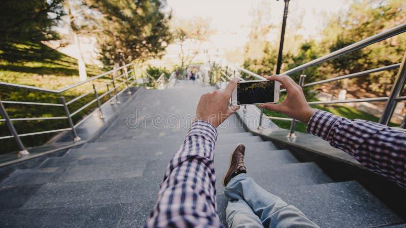 Slut upp en man som tar foto av den trevliga sikten med hans smarta telefon, medan sitta på trappa arkivbilder