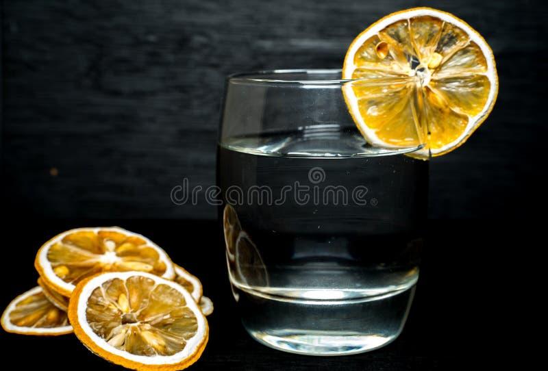 Slut upp exponeringsglas av vatten med den torkade citronskivan i tillbaka royaltyfri foto